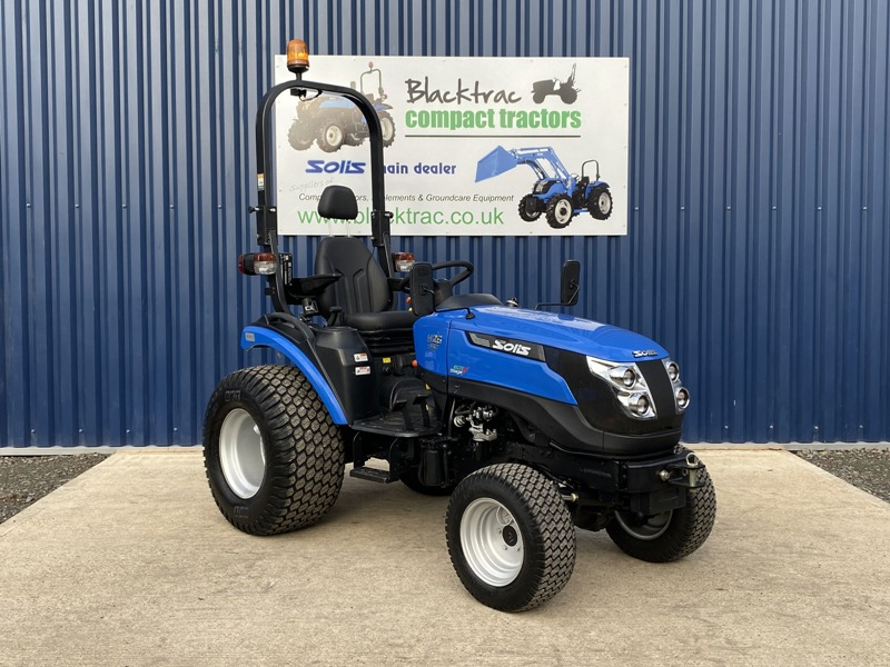 Blue Solis compact tractor side view outside Blacktrac.